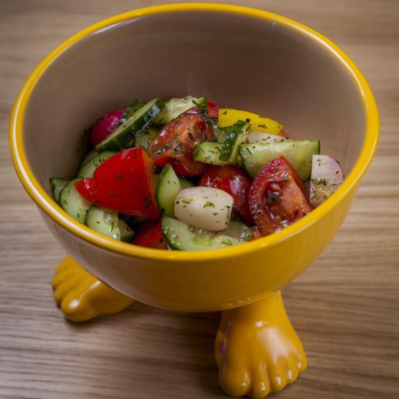 Овощной салат Помигурчик растет на маслянистой поверхности Овощ. Подается кусочками вместе с яркими растительными ломтиками редосом и пурцом